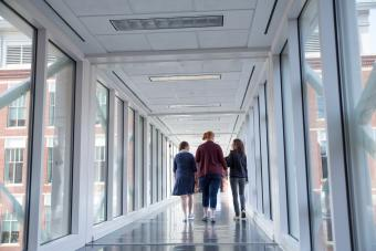 Three people walking in the school of medicine